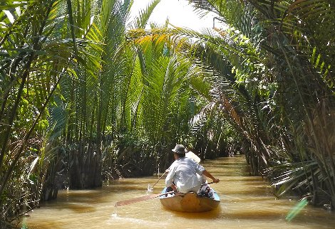 Boat passing through the Green Cathedral in Kampot